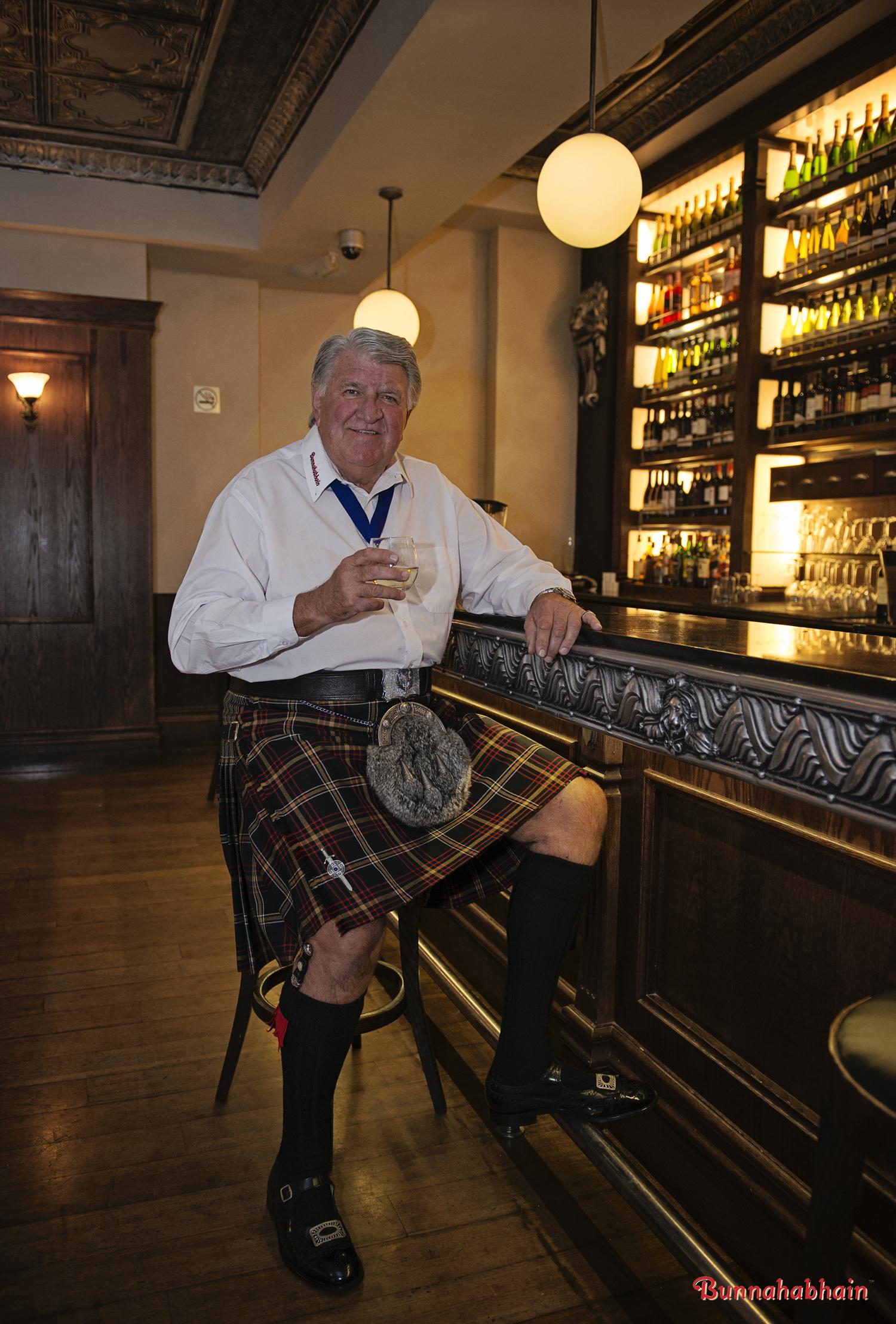 Kilted gentleman at bar enjoying whisky